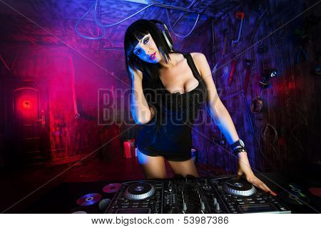 Beautiful sexual DJ girl working on a party in the old garage.