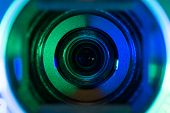 picture of feeding  - Video camera lens closeup lit in green and blue - JPG