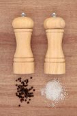 stock photo of condiment  - Salt and pepper grinders with loose condiments over papyrus background - JPG