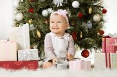 pic of solemn  - one-year-old little girl solemnize Christmas sit under Christmas-tree with gift