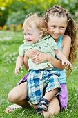 Little smiling girl sits squatted on grassy lawn, holding younger brother on knee