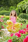 Little girl dressed in gown with puffy hem stands on sunny lawn among flowers