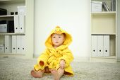 Little cute baby in yellow robe sits on white carpet in room at home. Shallow depth of field.