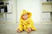 Little cute baby in yellow robe sits on white carpet and looks away in room at home. Shallow depth o