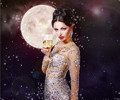 pic of sorcery  - Romantic girl in the beautiful dress with a glass of champagne against the night sky with magical stars and moon - JPG