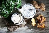 stock photo of sackcloth  - Teapot and cup of tea with milk and spices on sackcloth of wooden table - JPG
