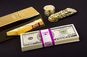 stock photo of inference  - Gold coins and a gold bar with a pile of American cash for use as any investment or transactional inference - JPG