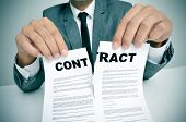stock photo of contract  - man wearing a suit sitting in a table ripping up a contract - JPG