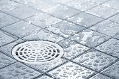 stock photo of water-saving  - Floor drain running water in shower tinted black and white image - JPG