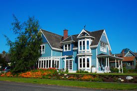 stock photo of victorian houses  - Bright blue house in sunlght with colorful poppies and some graceful trees - JPG