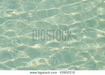 Crystal clear sea water in shallow sea on sand beach