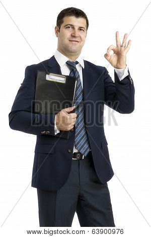Businessman With A Clipboard Saying Ok Isolated On White Background