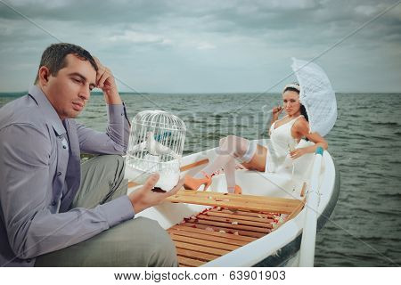 Romantic young couple in rowboat at lake