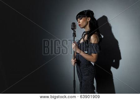 Young Singer with microphone over back background