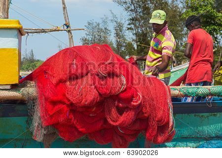 WELIGAMA, SRI LANKA - MARCH 7, 2014: Fisherman preparing fishing net on a boat. Tourism and fishing are two main business in this town.