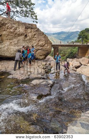 RAVANA FALLS, SRI LANKA - MARCH 2, 2014: Local tourists at Ravana falls, popular sightseeing attraction and one of the widest falls in the country.