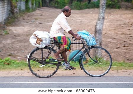 WELIGAMA, SRI LANKA - MARCH 7, 2014: Local man rides a bicycle on local road. Cycling is the main transportation for the traditional people in the country.