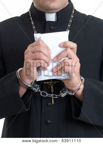 Catholic priest handcuffed holding envelope staffed with bribe money