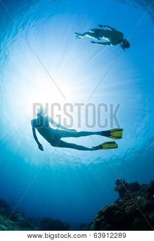 Underwater shot of the couple gliding in depth of tropical sea