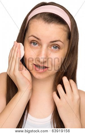 Teenage girl cleaning face with cotton pad on white background