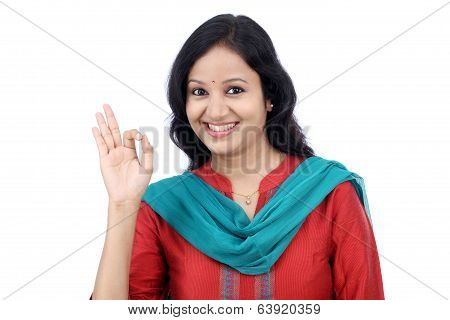 Cheerful young woman showing OK sign