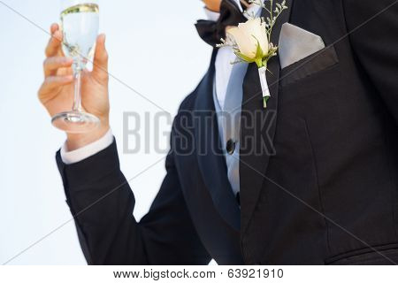 Close-up mid section of beautiful flowers on lapel of male as he holds champagne glass
