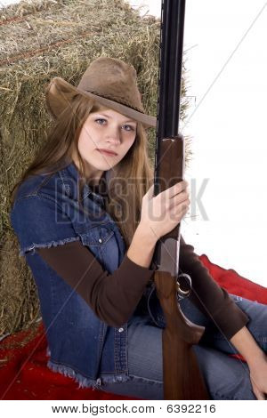 Woman Holding Gun Sitting On Red Blanket
