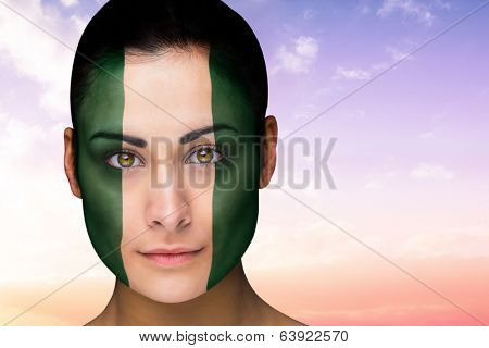 Composite image of beautiful brunette in nigeria facepaint against beautiful orange and blue sky