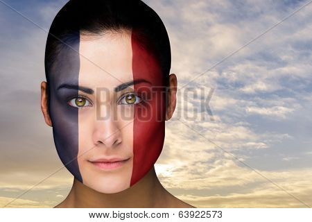 Composite image of beautiful brunette in france facepaint against scenic landscape with blue cloudy sky