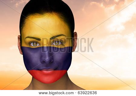 Composite image of beautiful brunette in colombia facepaint against beautiful orange and blue sky