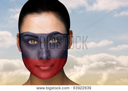 Composite image of beautiful brunette in russia facepaint against beautiful blue sky with clouds