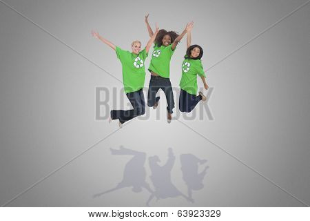 Composite image of enviromental activists jumping and smiling against grey vignette
