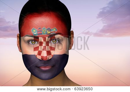 Composite image of beautiful brunette in croatia facepaint against beautiful orange and blue sky