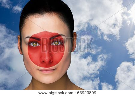 Composite image of beautiful brunette in japan facepaint against bright blue sky with clouds