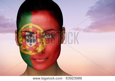 Composite image of beautiful brunette in portugal facepaint against beautiful orange and blue sky