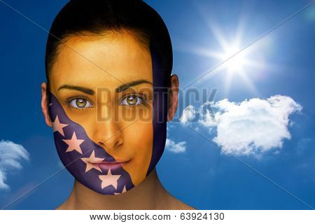 Composite image of beautiful brunette in bosnia facepaint against bright blue sky with clouds