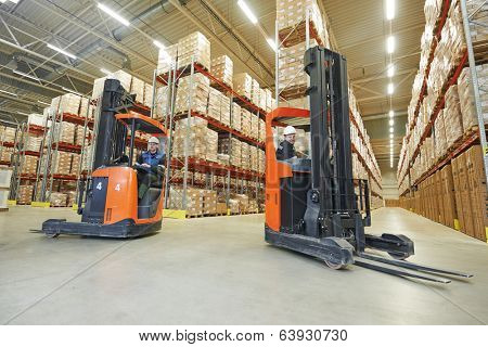 two young workers men in uniform at warehouse with forklift facilities