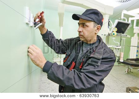 Carpenter joiner electrician with examining electric equipment at surgery room in clinic