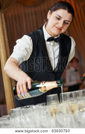 female waitress pour a glass of champagne during catering service at party