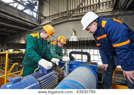 industrial workers with spanner at factory construction workshop