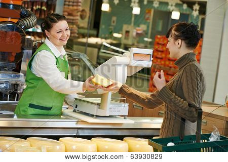 Sales assistant in supermarket demonstrating food cheese to female customer during shopping at store