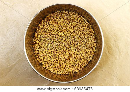 close up of fenugreek seeds in a cup taken on an isolated background