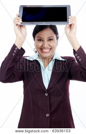 Angry businesswoman throwing her tablet computer