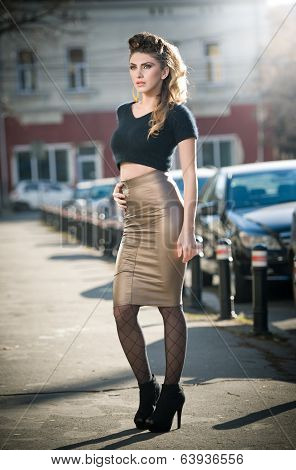 Attractive young woman in a urban fashion shot. Beautiful fashionable young girl with tight skirt