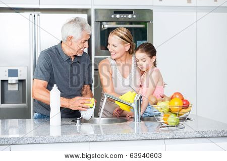 Grandparents and little girl washing dishes