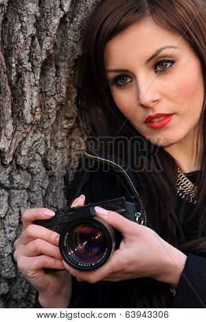 Young brunette girl using a classic camera