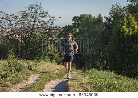 Long Haired Athlete Running In A City Park