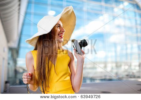 Young Traveling Woman With Photo Camera And Panama Dressed In Yellow Dress Standing In Front Of The
