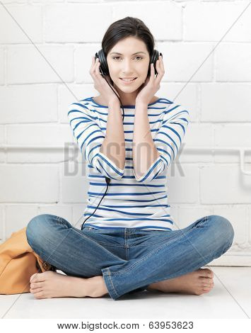 technology and music concept - picture of happy teenage girl in big headphones