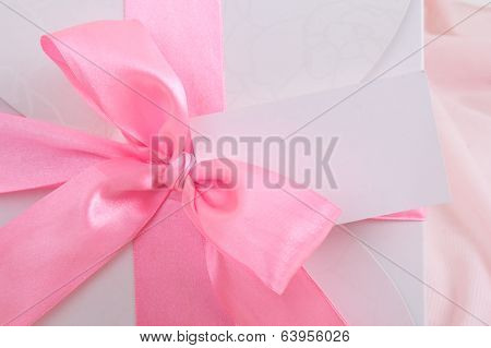 Close Up Of Gift Box With Pink Ribbon And Blank Card